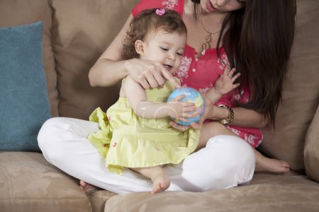 Mother teach and showing to his little daughter world globe