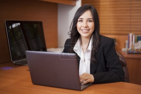 Businesswoman sitting at table in office lobby and using laptop