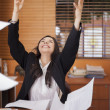 Young woman and flying papers in office...