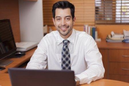 Photo pour Portrait d'un homme d'affaires mature heureux qui travaille avec un ordinateur portable dans un bureau lambrissé de bois - image libre de droit