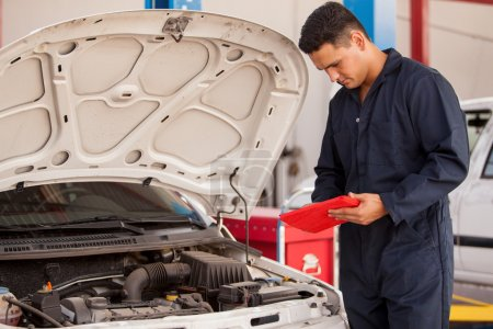 Photo for A mechanic checks the engine in auto repair service. - Royalty Free Image