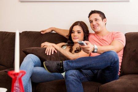 Photo pour Heureux couple hispanique s'amuser et regarder la télévision dans le salon - image libre de droit
