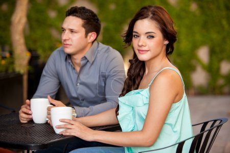 Photo for Cute young brunette drinking coffee on a first date - Royalty Free Image