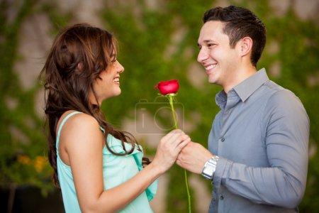 Photo pour Belle brune obtenant une rose rouge de sa date et souriant - image libre de droit