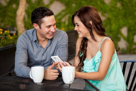 Woman showing something to her boyfriend on her cell phone