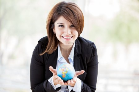 Attractive young business woman holding a small glowing globe