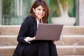 Usmívající se žena podnikání pomocí přenosného počítače