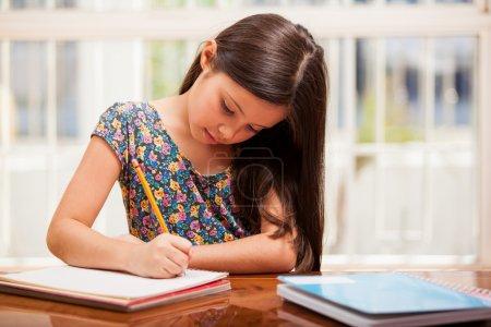 Photo pour Une petite fille fait ses devoirs - image libre de droit