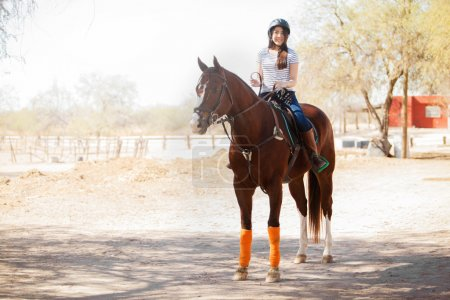 Woman in a helmet riding a horse