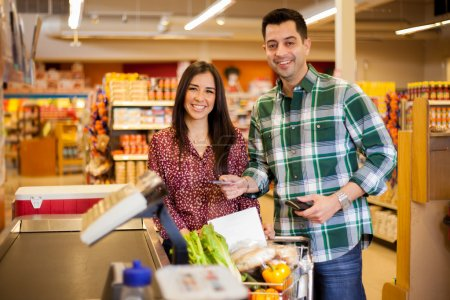 Cute  young couple standing with a trolley with products in the store at checkout and man  paying with credit card
