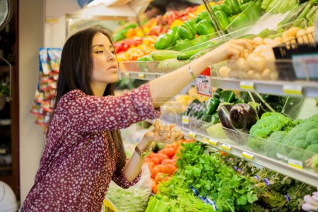 Photo for Cute brunette buying some groceries - Royalty Free Image