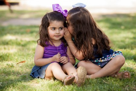 Cute little friends telling each other a secret while sitting at a park