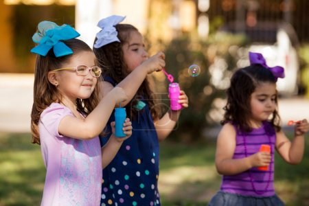 Beautiful little friends playing with bubbles on a sunny day at a park