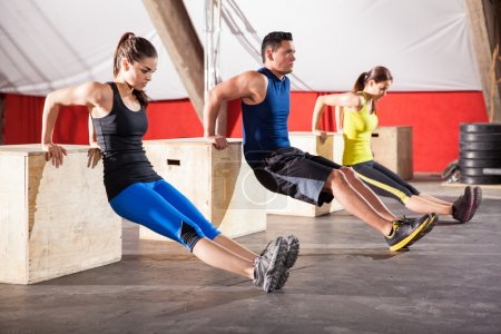 Photo for Group of young people working out their arms using boxes in a crossfit gym - Royalty Free Image