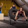 Happy people working out in a cross-training gym u...