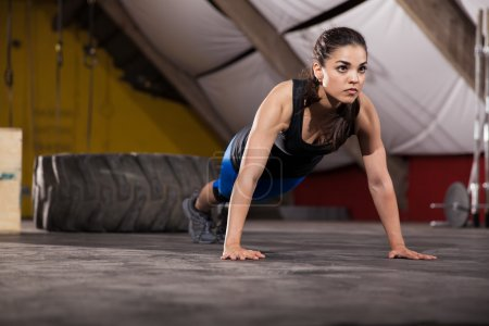 Photo for Gorgeous and strong brunette doing a set of push ups in a crossfit gym - Royalty Free Image