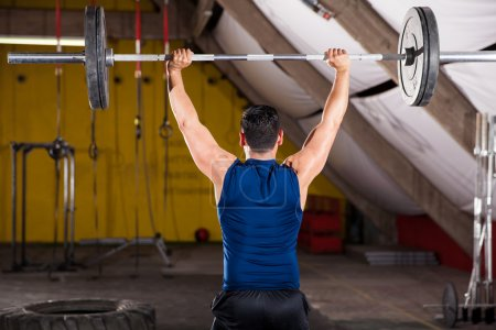 Photo for Rear view of a strong man lifting a heavy barbell in a cross-training gym - Royalty Free Image