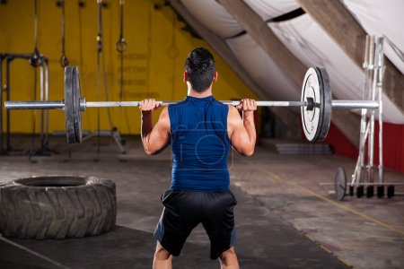 Photo for Strong young man lifting a barbell with weights as part of the WOD in a crossfit gym - Royalty Free Image