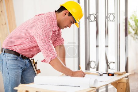 Handsome Hispanic engineer doing some design work and remodeling a house
