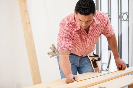 Male Hispanic contractor using a tape measure on a wood board at work