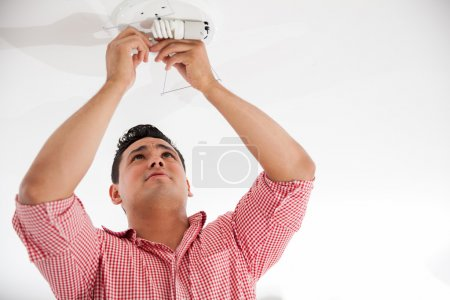 Young Hispanic man replacing some light bulbs from a lamp on the ceiling