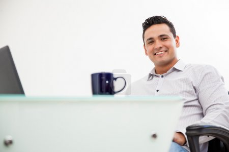 Portrait of a young Latin man working at his office and drinking coffee