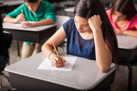 Photo pour Groupe d'élèves du secondaire qui passent un test en classe - image libre de droit