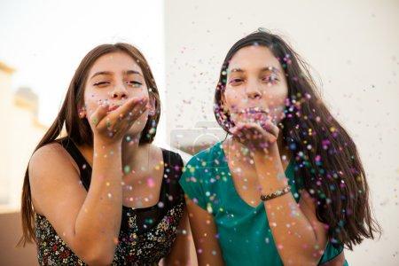 Friends blowing some confetti