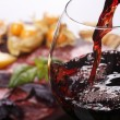 Pouring wine into glass and food background...