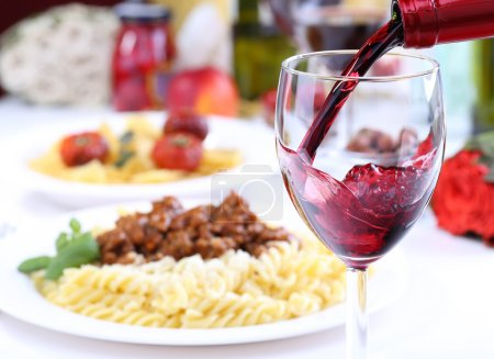 Photo for Pouring red wine and food background - Royalty Free Image