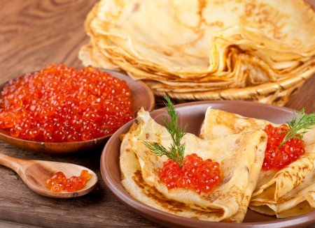 Pancakes with red caviar on wooden ware...