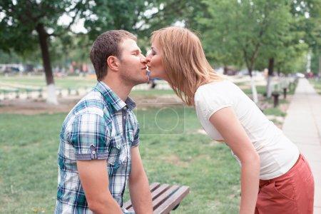 Photo pour Jeune couple baisers sur banc dans parc - image libre de droit