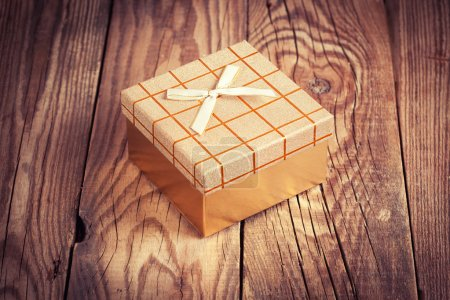 golden gift box on wooden background