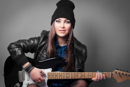 Photo for Beautiful young woman sitting with guitar on grey background - Royalty Free Image