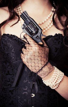 Photo pour Femme portant corset noir et perles et tenant un pistolet sur fond rétro - image libre de droit