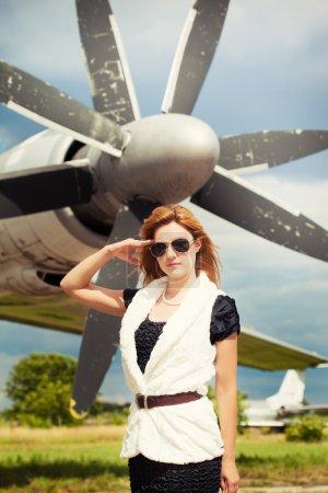Photo pour Belle femme portant des lunettes de soleil contre avion - image libre de droit