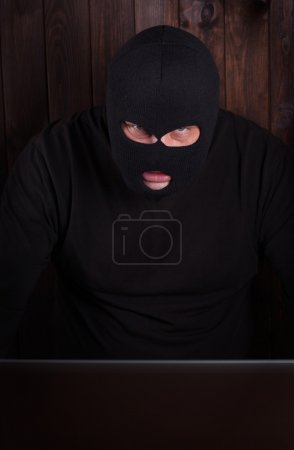 Photo pour Hacker dans une cagoule debout dans l'obscurité furtivement voler des données d'un ordinateur portable sur fond en bois - image libre de droit