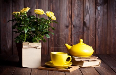 Photo for Yellow roses in pot, teapot, tea cup and old books on wooden table - Royalty Free Image