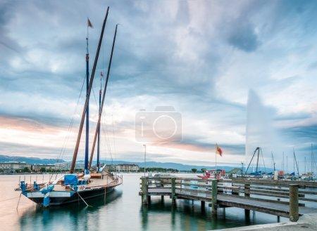 Photo pour Coucher ou lever de soleil vue de la célèbre fontaine dans la ville de Genève et du bateau dans le lac Léman. nuages bleus en arrière-plan. Suisse, europe. - image libre de droit