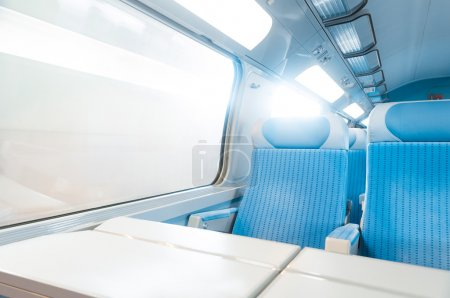 Photo for Inside cabin of modern express train. Nobody in blue chairs at window. Motion blur. Comfortable chairs and table in foreground, sun in background. Travel, France, Eu - Royalty Free Image
