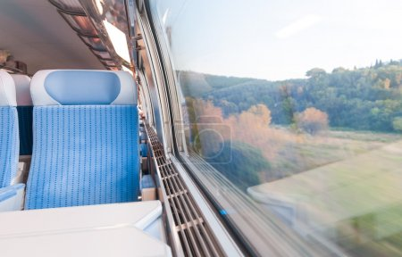 Photo for Inside cabin of modern express train. Nobody in blue chairs at window. Motion blur. Comfortable chairs and table in foreground, nature outside window. Travel, France - Royalty Free Image