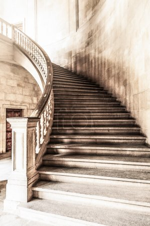 Photo for Marble winding staircase with high solid handrails in hall leading up. Vintage and grunge view of wide ancient stairway. Interior of old historical building in gloomy tints. - Royalty Free Image