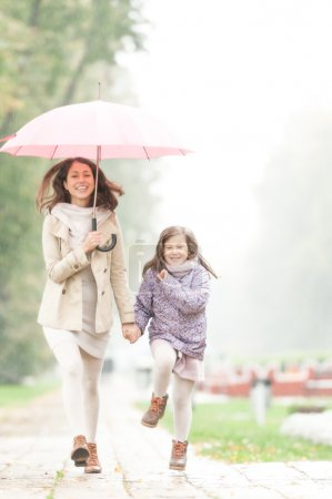 Mother and daughter with umbrella walking in park.