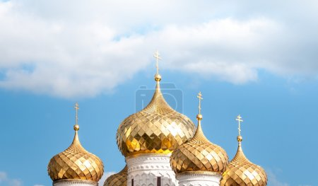 Golden domes of russian church against blue sky.