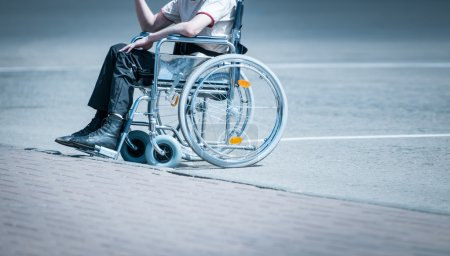Young man in wheelchair on the road alone.