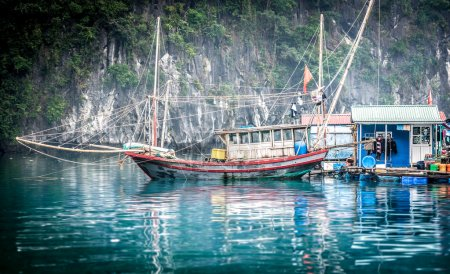 Photo for Floating fishing boat and houses in glittering blue waters of Halong Bay in Vietnam. Scenic background of rocky mountain with greenery on - Royalty Free Image