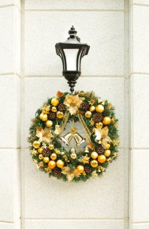 Christmas wreath on lantern on white wall.