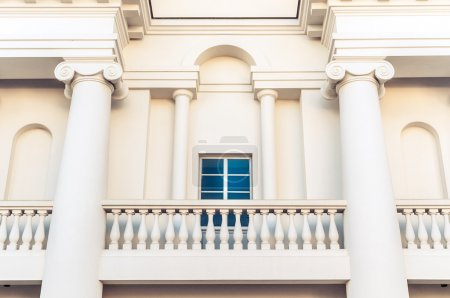 Photo for Detail of grand white building in classic style with balcony, square window and two big columns. Arch over window and from both sides from it. Architecture and facade of buildings. - Royalty Free Image