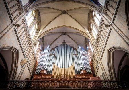 Photo pour Grand orgue à tuyaux sous le plafond voûté en église vieille-catholique qui brille au soleil. vue de dessous. plus grand instrument de musique utilisé principalement en service de l'église dans les pays occidentaux. - image libre de droit