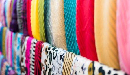 Photo pour Bouchent la vue de ligne coloré de nouvelles écharpes prêts pour la vente à la boutique. se concentrer sur celles de bleus et rouges. faire du shopping et vente au détail de vêtements décontractés. textiles et matières pour la vente. et du commerce. - image libre de droit
